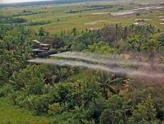A U.S. Army Huey helicopter sprays Agent Orange during
