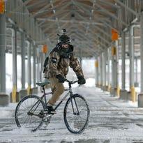 Glaser does a wheelie while biking on Pennsylvania Avenue outside the Rochester Public Market.