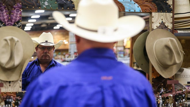 Terry Gibbs tries on a new hat before the San Angelo Stock Show and Rodeo starts Thursday, Feb. 1, 2018, at Cavender's Western Outfitter.