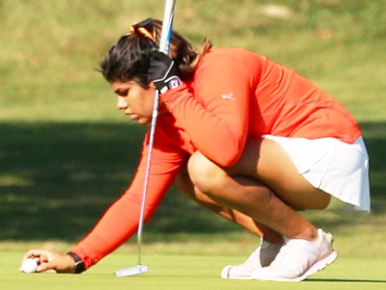 Northville's Sufna Gill marks her ball on the putting