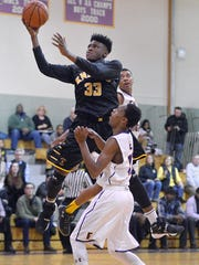 McQuaid's Isaiah Stewart drives for a layup over East's Windell Lucas earlier this month.