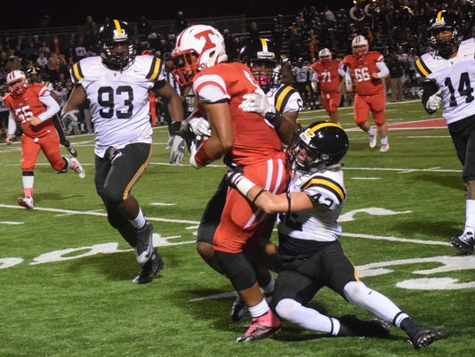 Tioga's Christian Smith (6, left) scores a first down as Neville defender Luke Cagle (42, right) wraps him up.