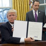 Trump wields his presidential pen, signing memos on trade, hiring, abortion