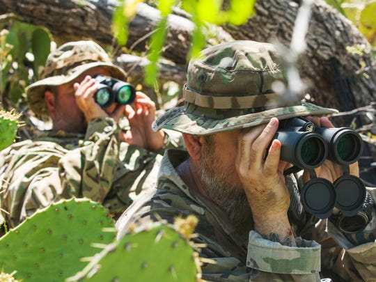 Arizona Border Recon volunteers Lorenzo Murillo (right) and Calvin Stowers use binoculars to look into the Mexico border mountains for smugglers or drug traffickers illegally crossing into the U.S.  Some Californians are working to relaunch the Minuteman patrol movement.