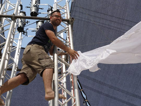 Justin Commu of Toronto works on a metal tower inside the Opulent Chill campsite at Burning Man.
