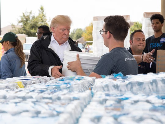 President Trump places supplies into cars at a relief