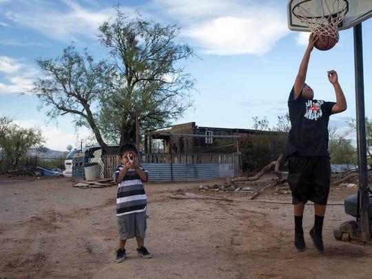 Darryn Cruz, 12, and nephew Kayden Cruz, 3, play at their home on tribal land in Sells, Arizona.