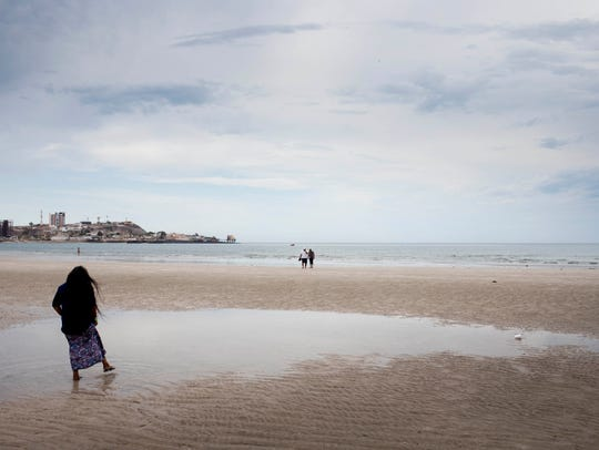 Thomasa Rivas walks on the beach after praying with