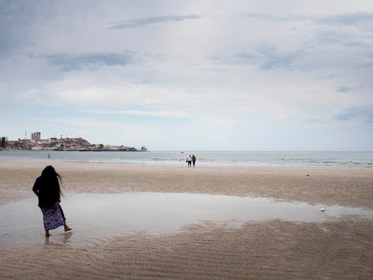Thomasa Rivas walks on the beach after praying with her family in Puerto Peñasco, Sonora. From here, she will travel to the sacred site of Quitovac.
