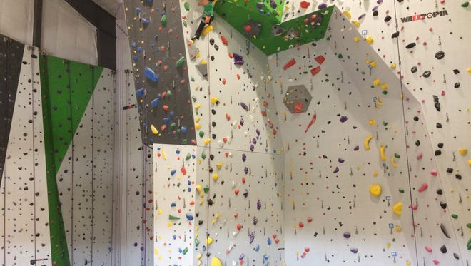 Yolanda Chen climbs the 60-foot wall at Onsight Rock Gym, while her husband Christian Robinson takes up the slack in the rope.