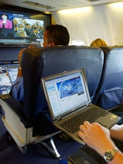 FILE - This is a  July 29, 2002  file photo of  a laptop is used on a plane . Britain's government  Tuesday March 21, 2017 banned electronic devices in the carry-on bags of passengers traveling to the U.K. from six countries, following closely on a similar ban imposed by the United States.