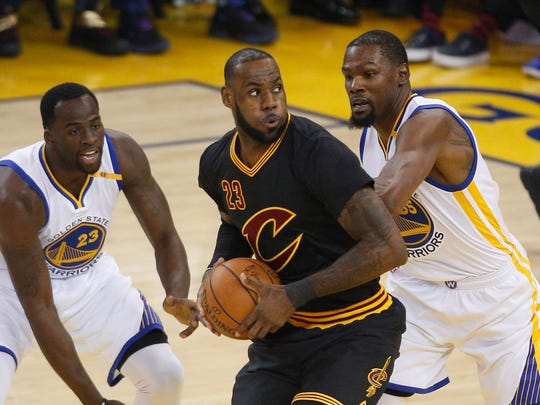Cleveland Cavaliers forward LeBron James (23) is defended by Golden State Warriors forward Draymond Green (23) and forward Kevin Durant (35).