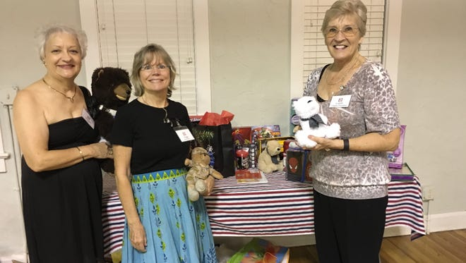 Three board members happily show some of the donated toys: Jennifer Snellson-Wells, chapter vice president; Peggy Goodknight, food and beverages; and Lorely Ridge, chapter president.