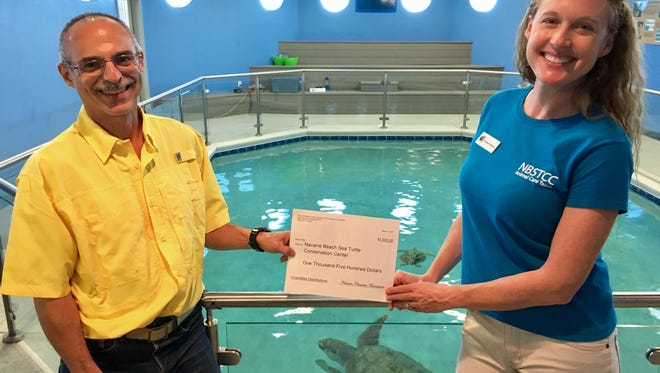 Mike Sandler, Navarre Beach Area Chamber of Commerce Foundation, and Cinnamon Holderman, Navarre Beach Sea Turtle Conservation Center, with Gigi the sea turtle.