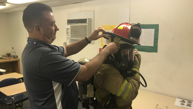 Mike Miller, formerly a lieutenant in the Abilene Fire Department, helps Abilene High School sophomore Cameron Mitchell into firefighting bunker gear.