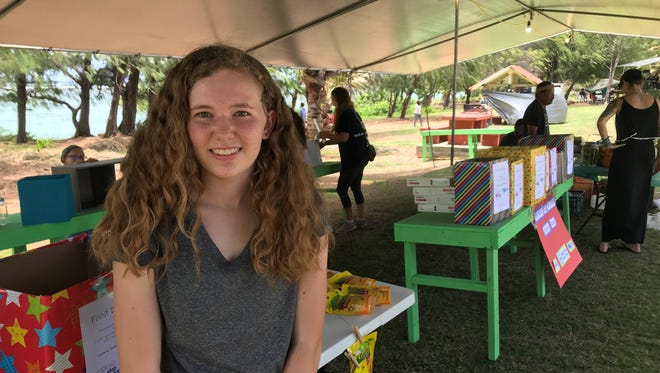 Faith Camper, 14, creator of Everybody Has Something Pantry Boxes sets up a booth to receive donations of nonperishable goods from the community at the 9th Annual Talofofo Banana Festival.