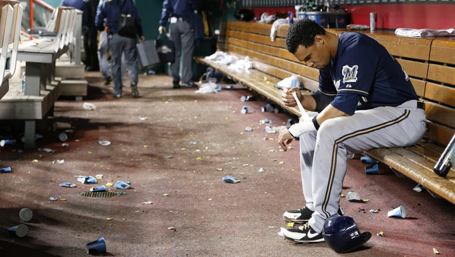 Brewers centerfielder Carlos Gomez sits in the dugout after a 3-1 loss to the Cincinnati Reds at Great American Ball Park on Sept. 23, 2014, in Cincinnati. The Brewers fell out of first place in their division, where the team had been for 150 consecutive days, on Sept. 1, 2014.