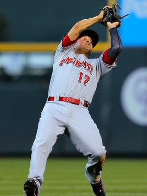 Cincinnati Reds second baseman Kris Negron falls back as he catches a pop fly.
