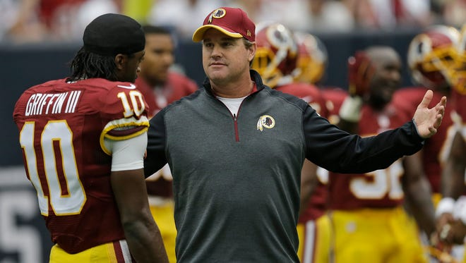FILE - In this Sept. 7, 2014, file photo, Washington Redskins head coach Jay Gruden talks to quarterback Robert Griffin III  before an NFL football game against the Houston Texans in Houston.