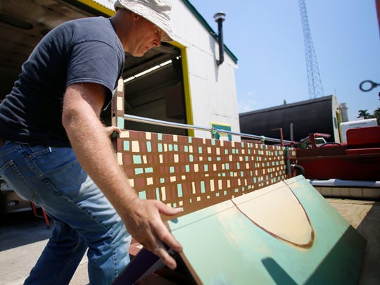 Using recycled boards, MSU Residential College in the Arts and Humanities academic specialist Steve Baibak puts a bench in the 1937 Ford fire engine he and some of his students have been refurbishing Wednesday in Haslett.  The old fire truck will become a mobile community art center, featuring a stage, microphones, bins for art supplies, and a large chalk board.