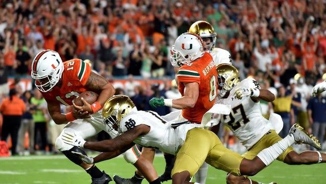 Nov 11, 2017; Miami Gardens, FL, USA; Miami Hurricanes quarterback Malik Rosier (12) scores a touchdown as Notre Dame Fighting Irish safety Devin Studstill (14) defends during the first half at Hard Rock Stadium. Mandatory Credit: Steve Mitchell-USA TODAY Sports