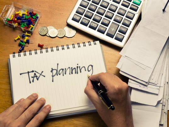 A man planning for his taxes with a notepad