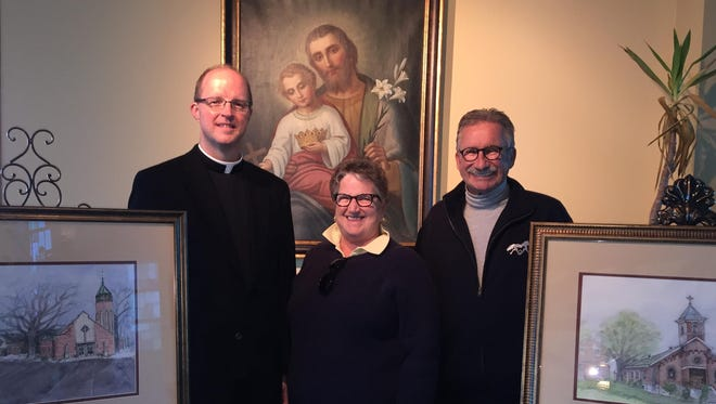 The Rev. Phillip De Vous, left, pastor of St. Joseph Parish in Crescent Springs, is joined by Marianne and Steve Fieger, of Fort Mitchell between paintings showing the original church 100 years ago and today's church. On Saturday, March 19, the parish kicked off its centennial celebration.