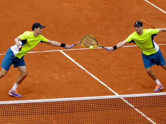 USA's Bob, left, and Mike Bryan return the ball to Spain's Marcel Granollers and Marc Lopez during their quarterfinal match of  the French Open tennis tournament at the Roland Garros stadium, in Paris, France, Monday, June 2, 2014. The Spanish pair won 6-4, 6-2. (AP Photo/Darko Vojinovic)