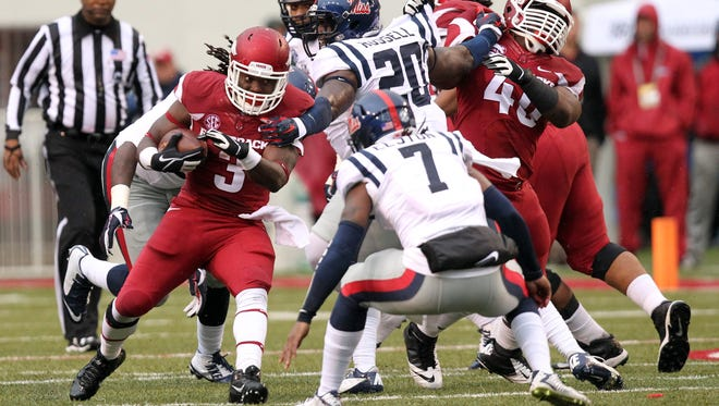 Arkansas Razorbacks running back Alex Collins (3) rushes during the first half as Ole Miss Rebels linebacker Christian Russell (20) and defensive back Trae Elston (7) defend at Donald W. Reynolds Razorback Stadium last week. Arkansas beat then-No. 8 Ole Miss, 30-0, for its second straight shutout win.