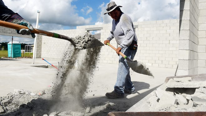 Lionel Lezama, with Cove Concrete & Co. in Vero Beach, cleans up after finishing the construction of the exterior wall of a new home July 6, 2017, in the Summer Lake subdivision north of Vero Beach. The subdivision sat dormant for several years until GHO Homes bought the land in 2015. Summer Lake will consist of 91 units, a dog and community park and a dock.