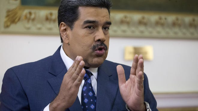 Venezuela's President Nicolas Maduro speaks during an interview with the Associated Press at Miraflores presidential palace in Caracas, Venezuela, Feb. 14, 2019. Even while criticizing Donald Trump's confrontational stance toward his socialist government, Maduro said he holds out hope of meeting the U.S. president to resolve an impasse over his recognition of opponent Juan Guaido as Venezuela's rightful leader.