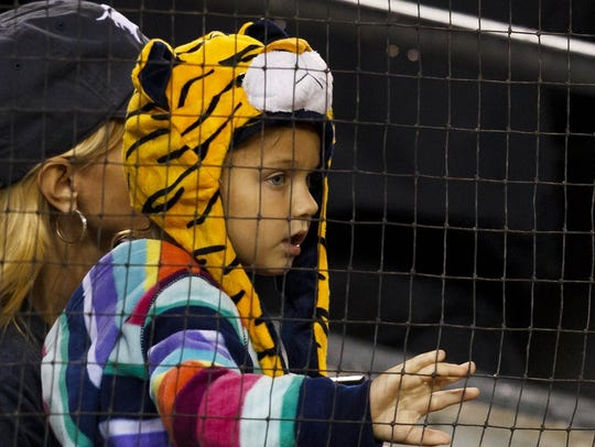 A young Detroit Tigers fan watches a game against the