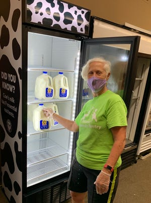 Jody Koenigseker, Alliance Community Pantry board member and volunteer coordinator, shows off the new milk cooler donated by the American Dairy Association.