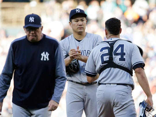New York Yankees starting pitcher Masahiro Tanaka, center, stands on the mound after a conference with pitching coach Larry Rothschild, left, and catcher Gary Sanchez (24) during the third inning of the team's baseball game against the Seattle Mariners, Saturday, July 22, 2017, in Seattle.