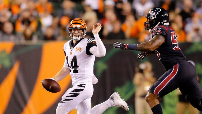 Cincinnati Bengals quarterback Andy Dalton (14) scrambles away from Houston Texans inside linebacker Benardrick McKinney (55) in the fourth quarter of the NFL Week 2 game between the Cincinnati Bengals and the Houston Texans at Paul Brown Stadium in downtown Cincinnati on Thursday, Sept. 14, 2017.
