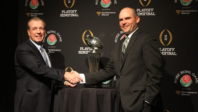 Oregon coach Mark Helfrich poses for a photo with Florida State coach Jimbo Fisher next to the Rose Bowl trophy on Wednesday, Dec. 31, 2014, in Los Angeles.