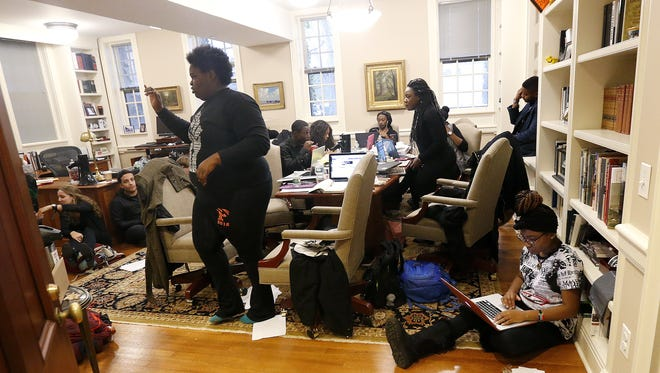Students are seen inside the office of Princeton University President Christopher Eisgruber, Wednesday, Nov. 18, 2015, in Princeton, N.J. The protesters from a group called the Black Justice League demand the school remove the name of former school president and U.S. President Woodrow Wilson from programs and buildings over what they said was his racist legacy. (AP Photo/Julio Cortez)