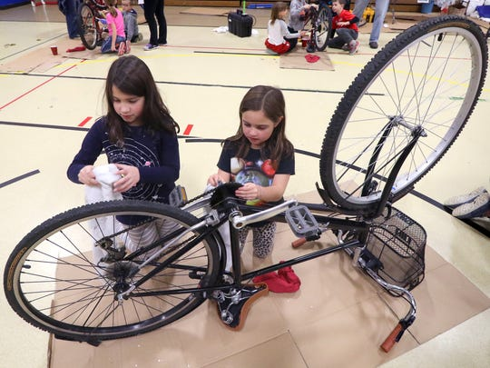 Second graders Amelia Ostrenga (left) and Sofia Astorga clean an abandoned bicycle to prepare it for donation during Wilson Elementary/Wilson STEM's Service Day with five different projects to benefit local  groups and American servicemen on Nov. 21.
