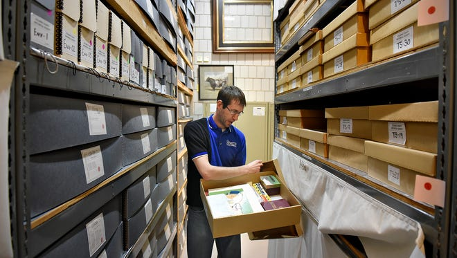 Curator of Collections Adam Smith looks through a box of items from the museum's collection Friday, May 20 at the Stearns History Museum in St. Cloud.