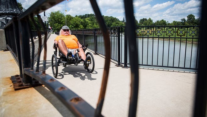 A cyclist wheels past a broken section of railing on the Veteran's Memorial Bridge Friday.