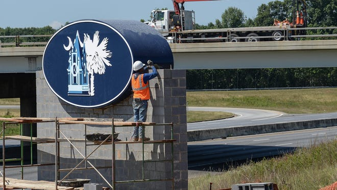 Brickmasons work on a welcome sign for Anderson County on I-85 Southbound, near the State Highway 153 exit, in Powdersville on Monday. The sign is expected to be completed this week.