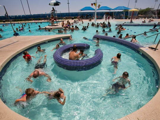 Children play in a packed pool during a 100 degree