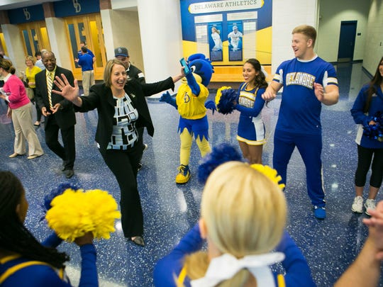 Chrissi Rawak comes out of her press conference and high-fives the University of Delaware cheerleading squad after being announced as UD's new athletic director on May 13, 2016.