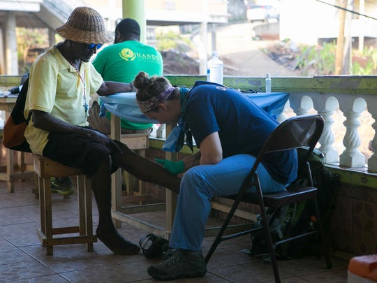Nurse practitioner Beth Sargent examines a patient with a cut on his leg as the Delaware Medical Relief Team sets up a second medical clinic in the village of Paix Bouche, Dominica.