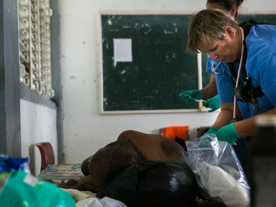 Nurse Andrea B. Jones and nurse practitioner Lyndsay Bingnear tend to the bed sores of a 73-year-old man in Portsmouth, Dominica.