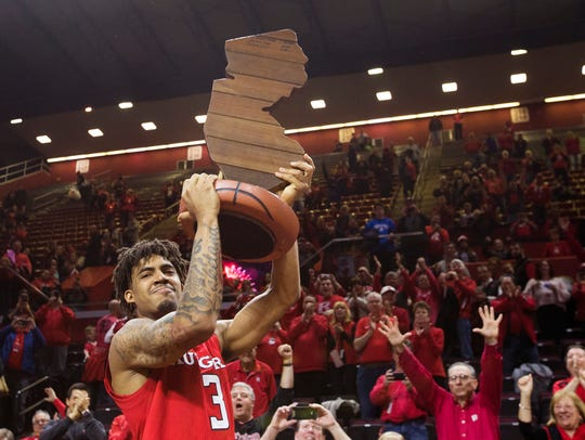 Rutgers' Corey Sanders holds up the game trophy after