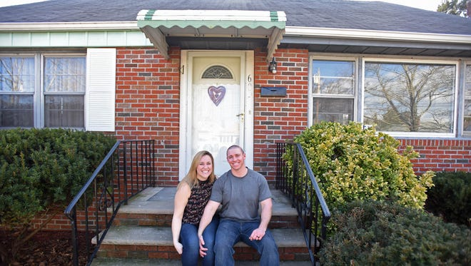 Laura and Dennis Hill in front of their newly purchased Cape Cod in Maywood.