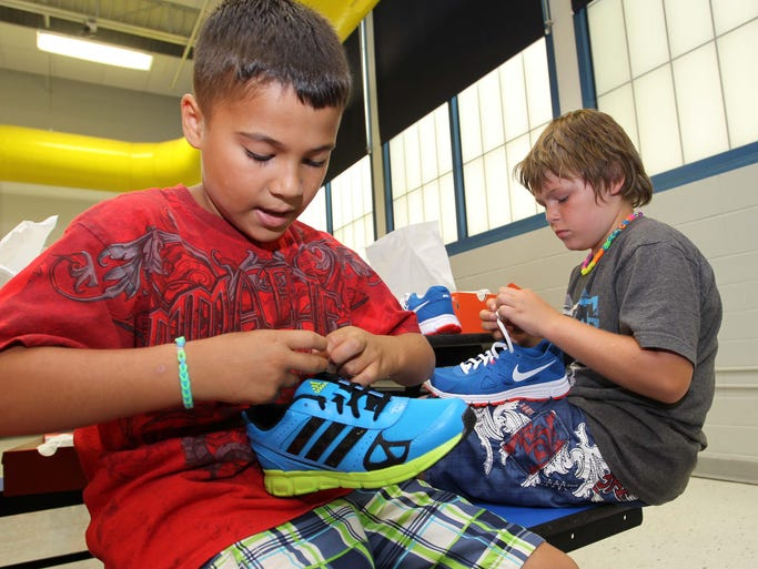 Brandon Catono, left, and Johnny Robbis recieve a new pair of shoes at the shoe giveaway event at McGregor Elementary in Springfield on July 7, 2014.