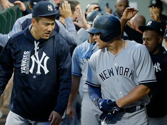 New York Yankees' Aaron Judge, right, is greeted in the dugout by pitcher Masahiro Tanaka, left, after Judge hit a three-run home run during the fifth inning of the team's baseball game against the Seattle Mariners, Friday, July 21, 2017, in Seattle. (AP Photo/Ted S. Warren)