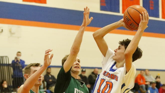 Nate Chorney of Thomas A. Edison puts up a shot as Newfield's Patrick King, center, and Patrick Banfield defend Wednesday during the Trojans' 54-35 victory in Elmira Heights.